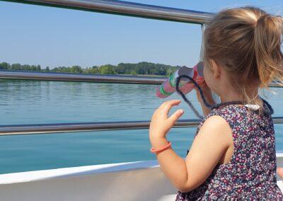 mit dem Fernglas ans Ufer schauen